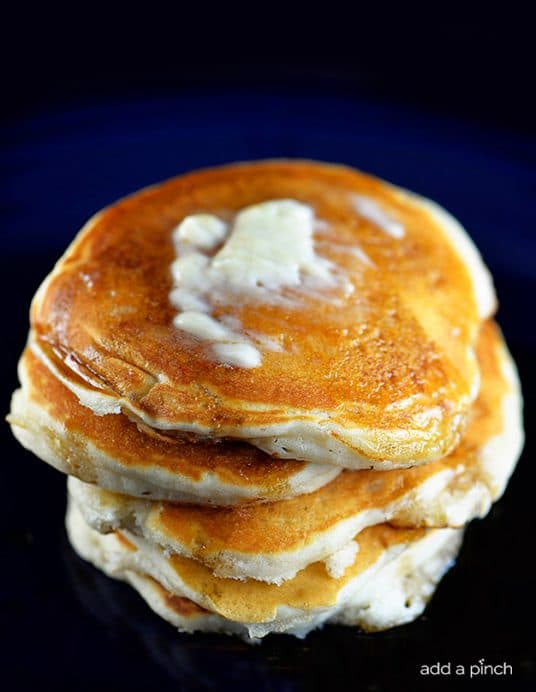 Photograph of buttermilk pancakes topped with butter and maple syrup. // addapinch.com