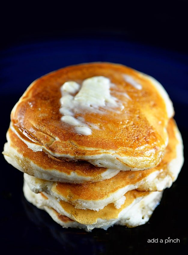 Photograph of stack of buttermilk pancakes topped with butter and maple syrup on a blue plate. // addapinch.com