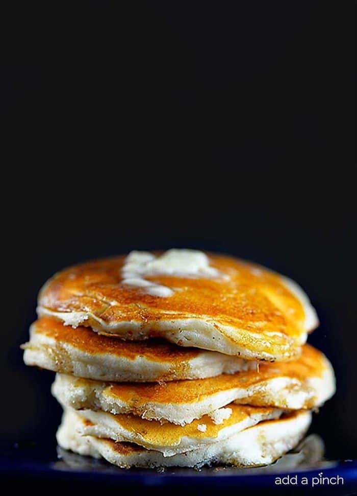 Closeup photograph of stack of buttermilk pancakes with butter and maple syrup. // addapinch.com