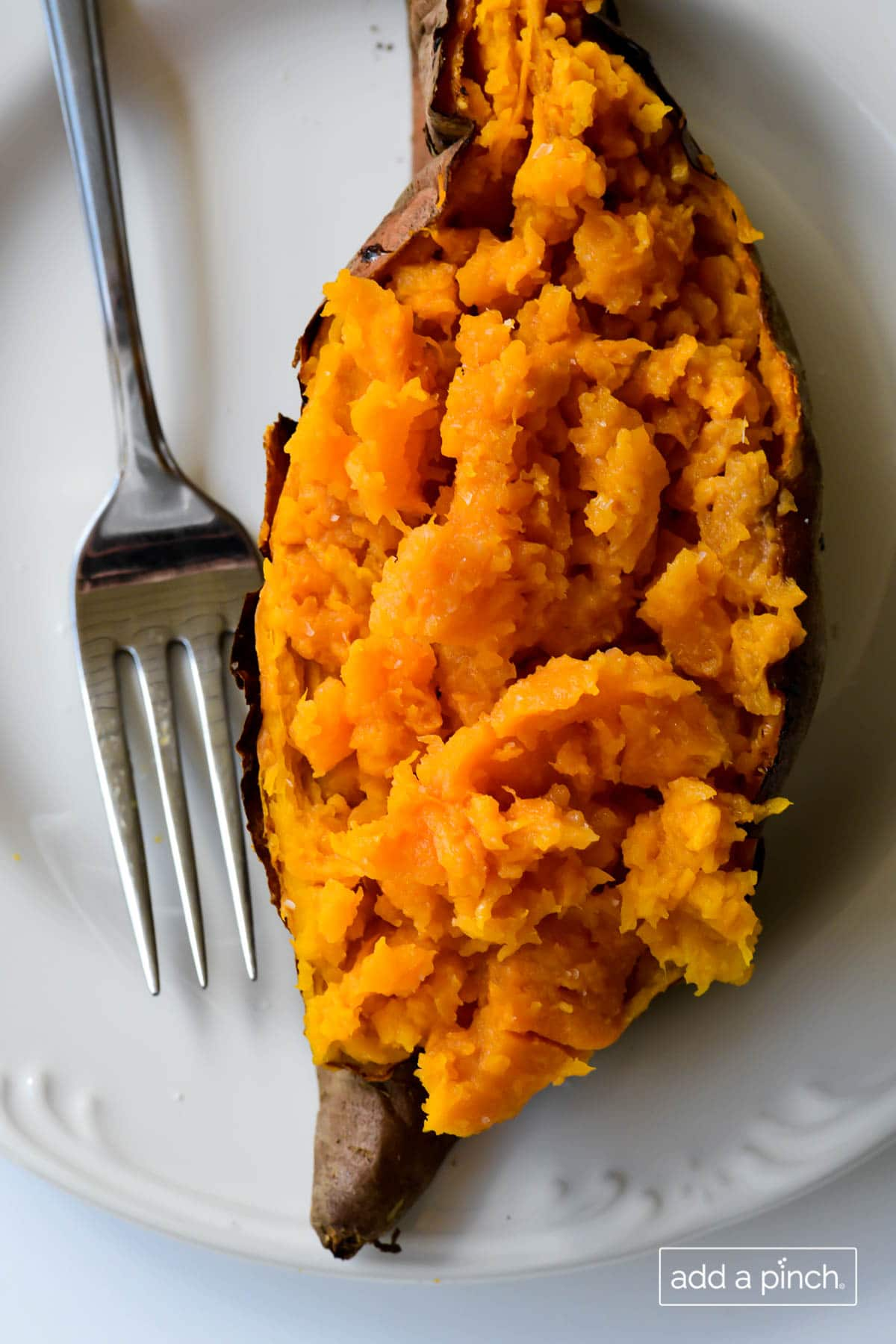 Overhead photograph of baked sweet potato on a white plate.