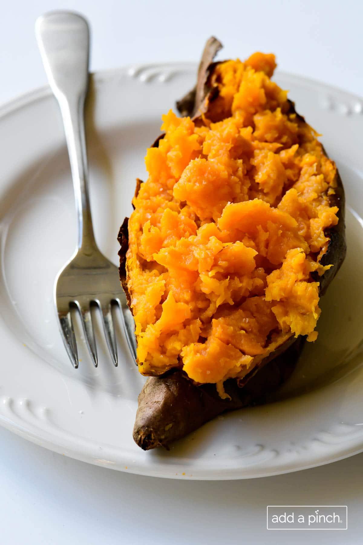 Photograph of baked sweet potato on a white plate with fork.