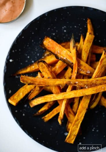 Photograph of sweet potato fries on a black plate on a white background.