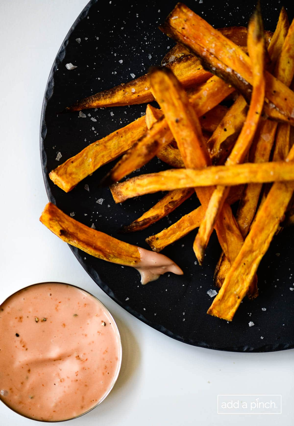 Closeup photograph of sweet potato fries on a black plate served with comeback sauce.