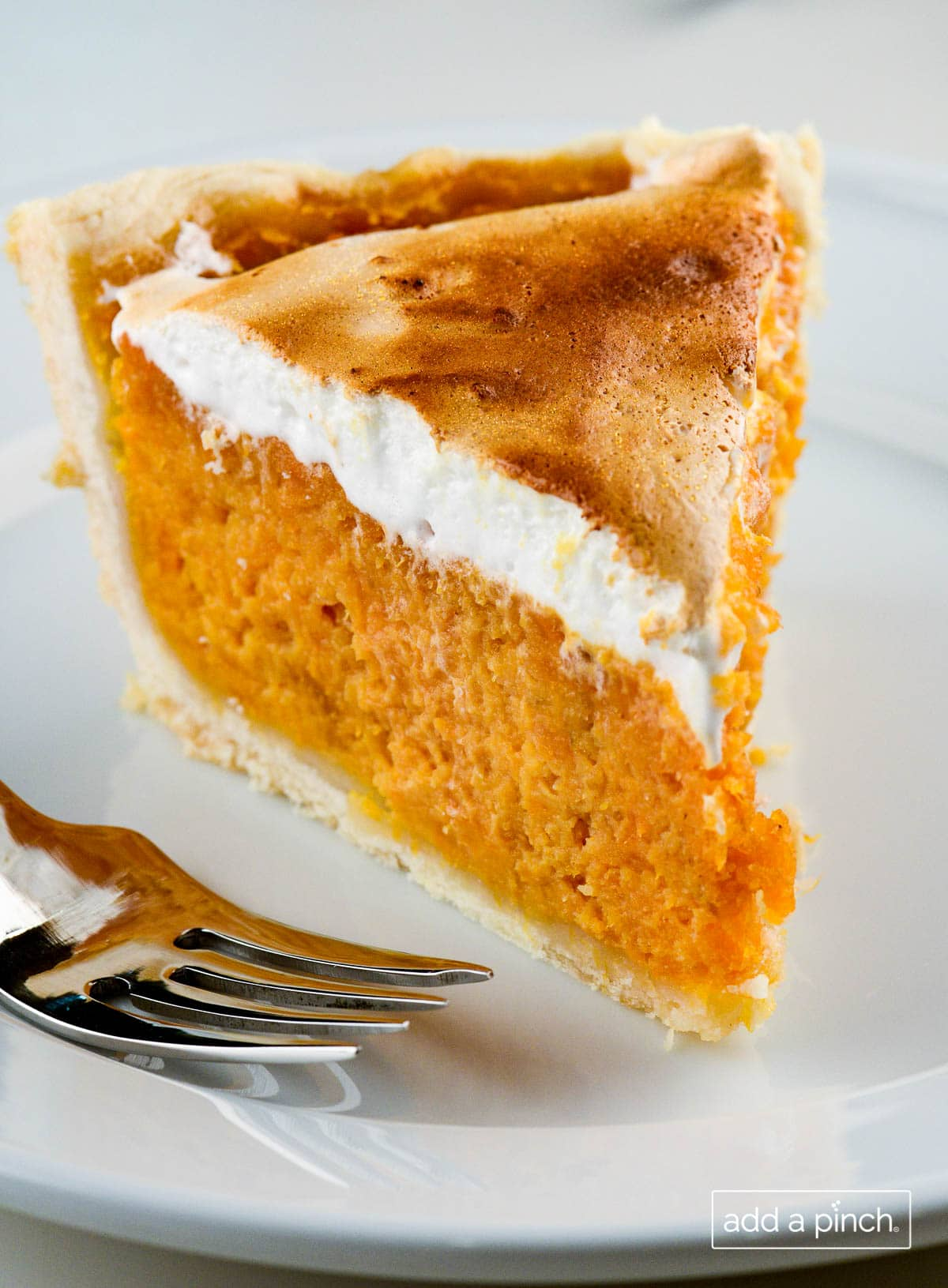 Photograph of slice of sweet potato pie with toasted marshmallow fluff topping.