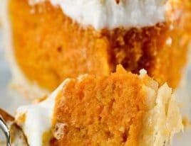 Closeup photograph of slice of sweet potato pie on a white plate.